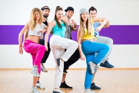Photo pour Jeunes hommes et femmes dansant la zumba chorégraphie de groupe moderne à l'école de danse - image libre de droit