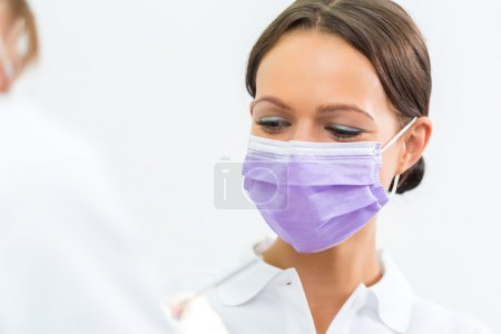Dentist in her practice giving dental treatment