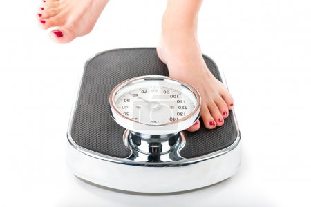 Photo for Diet and weight, young woman standing on a scale, only feet to be seen - Royalty Free Image