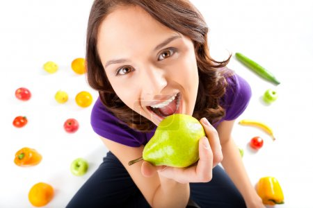 Photo for Healthy eating, happy woman with fruits and vegetables is eating a pear - Royalty Free Image