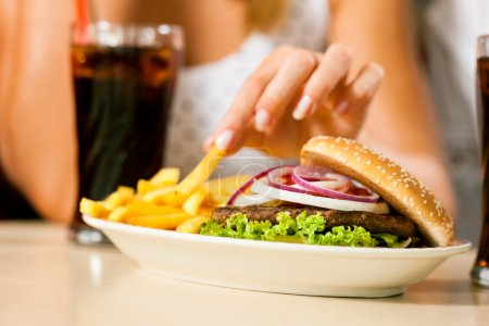 Photo for A woman eating hamburger and drinking soda in a fast food diner; focus on the meal - Royalty Free Image
