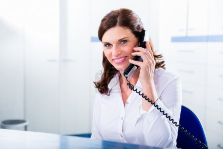 Doctors nurse with telephone in front desk