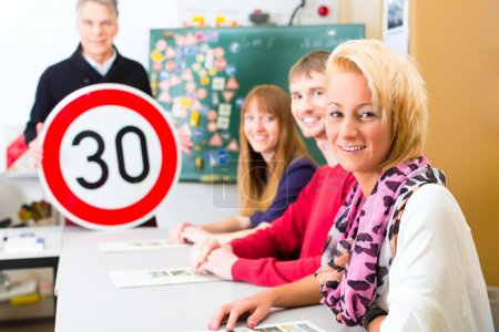 Photo for Driving school - driving instructor and student drivers with a tempo thirty Road sign, in the background are traffic signs - Royalty Free Image