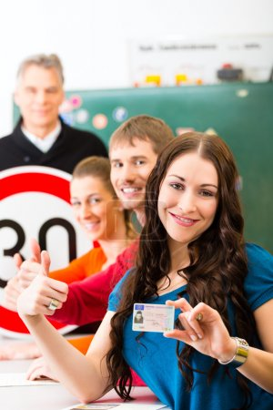 Photo for Driving school - driving instructor in his class and a female student driver looking in the Camera, in the background are traffic signs - Royalty Free Image