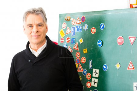 Photo for Driving school - driving instructor in his class, he standing in front of a blackboard and looking in the camera, in the background are traffic signs - Royalty Free Image