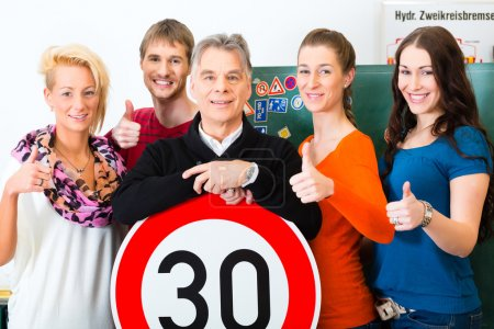 Photo for Driving school - driving instructor and student drivers look at a tempo thirty Road sign, in the background are traffic signs - Royalty Free Image