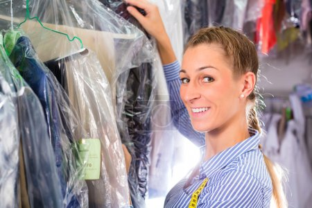 Photo for Female cleaner in laundry shop or textile dry-cleaning next to clean clothes in garment bags - Royalty Free Image