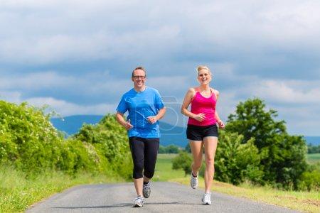 Photo pour Couple, homme et femme faisant du jogging ou du sport en plein air pour la forme physique dans la rue rurale - image libre de droit