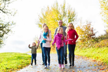 Family taking walk in autumn forest
