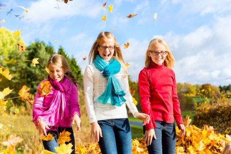 Friends romping in harvest leaves throwing foliage
