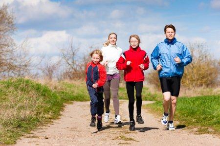 Photo pour La famille, la mère, le père et les enfants courent ou font du jogging pour le sport à l'extérieur - image libre de droit