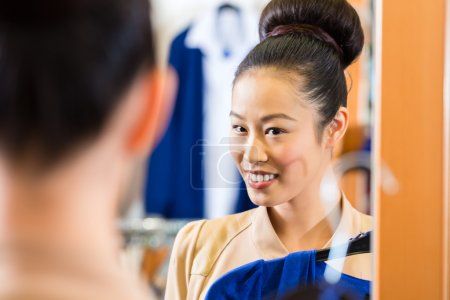Asian Woman trying clothes in shop mirror