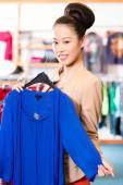 Asian Woman choosing clothes in fashion shop