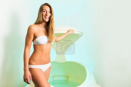 Wellness - young woman floating in Spa in bathtub
