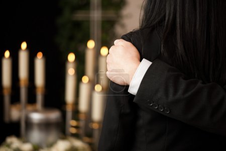 Religion, death and dolor  - couple at funeral con...