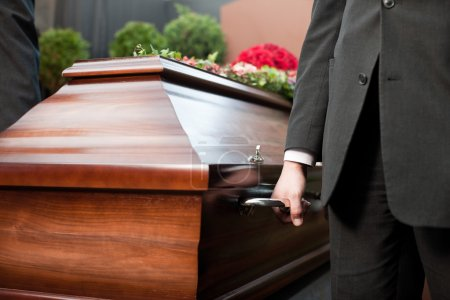 Photo for Religion, death and dolor  - coffin bearer carrying casket at funeral to cemetery - Royalty Free Image