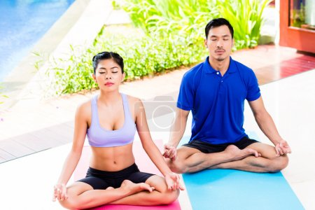 Asian yoga couple in lotus seat mediating