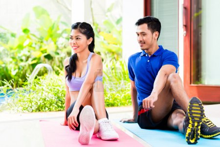 Asian fitness couple doing stomach crunches