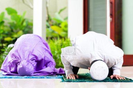 Photo pour Couple musulman asiatique, homme et femme, prier à la maison assis sur des tapis de prière dans leur maison en face du jardin tropical - image libre de droit