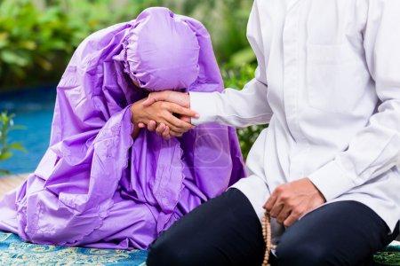 Photo pour Couple musulman asiatique, homme et femme, priant à la maison assis sur le tapis de prière dans leur maison en face du jardin tropical - image libre de droit