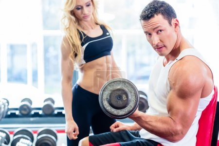 Photo for Couple in fitness gym with dumbbells lifting weight as sport, man and woman training together - Royalty Free Image