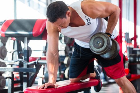 man with dumbbells at sport in fitness gym