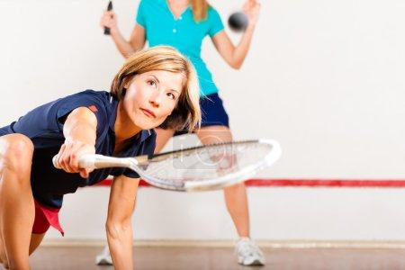 Photo pour Deux femmes jouant au squash comme sport de raquette au gymnase, ça pourrait être une compétition. - image libre de droit