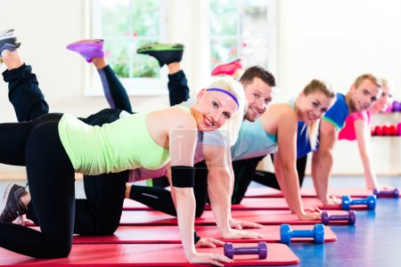 Photo for Fitness people in gym working out with dumbbells - Royalty Free Image