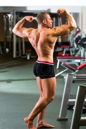 Photo for Strong man, bodybuilder posing in Gym, workout equipment in the background - Royalty Free Image