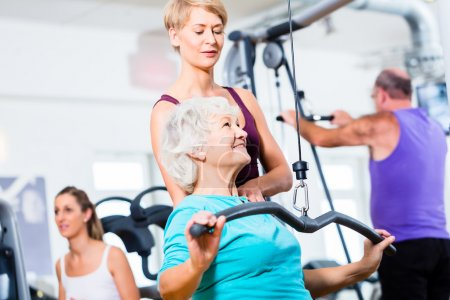 Senior woman doing back training with trainer in gym