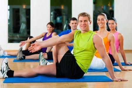 Photo pour Groupe de cinq personnes fait des exercices d'étirement au club de remise en forme sur des nattes de gym - image libre de droit