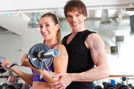 Sport - couple is exercising with barbell in gym