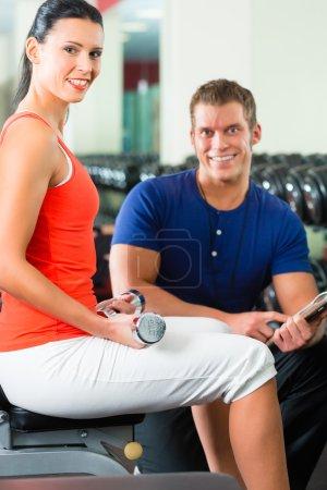 Photo pour Femme avec son entraîneur de fitness personnel dans la salle de gym exercice avec haltères - image libre de droit