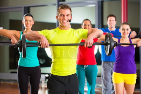 Photo for Group of young sport people training with barbell at a gym for better fitness - Royalty Free Image