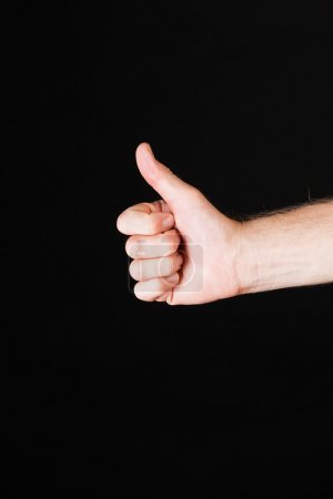 Photo for Male Caucasian hand showing thumbs up in front of black background - Royalty Free Image