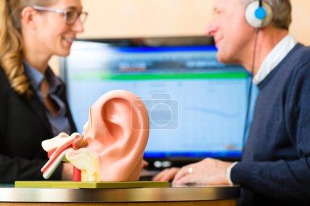 Photo pour Homme plus âgé ou un pensionné avec un problème d'audition faire une audition à tester et peut-être besoin d'une prothèse auditive, au premier plan est un modèle d'une oreille humaine - image libre de droit