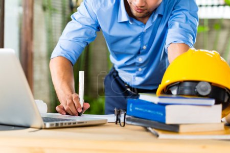 Photo for Freelancer - Architect working at home on a design or draft, on his desk are books, a laptop and a helmet or hard hat - Royalty Free Image
