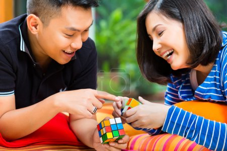 Photo for Young Indonesian couple - man and woman - at home playing with a magic cube - Royalty Free Image