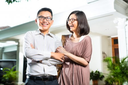 Asian homeowner couple in front of home