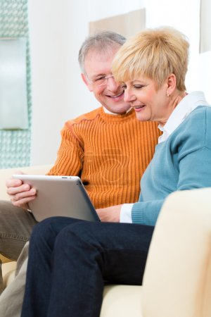 Seniors at home with tablet computer