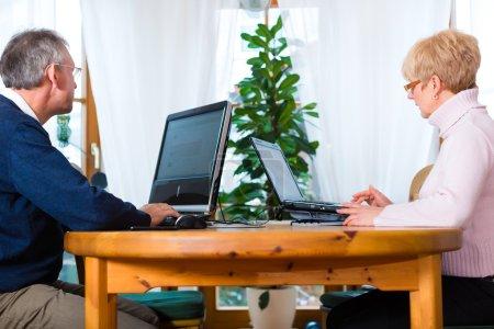 Aînés à domicile travaillant sur ordinateur