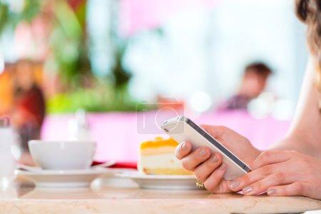 Photo pour Jeune femme dans un café ou un salon de crème glacée utilisant son téléphone, peut-être qu'elle est célibataire ou attend quelqu'un - image libre de droit