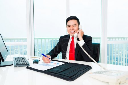 Business man telephoning in office controlling profit