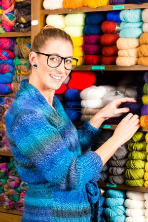 Young woman in knitting shop