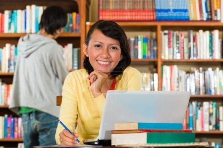 Chica joven en la biblioteca con el portátil