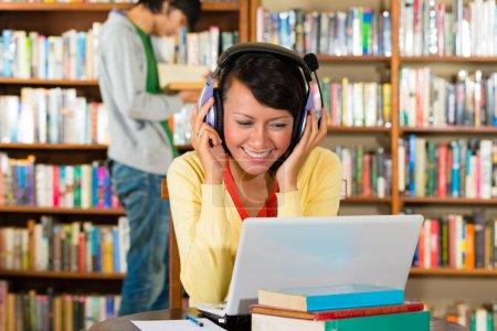 Photo pour Étudiant - Jeune femme à la bibliothèque avec ordinateur portable et casque d'apprentissage, un étudiant masculin debout en arrière-plan lit un livre - image libre de droit