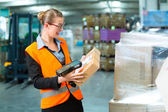 Female worker scans package in warehouse of forwarding