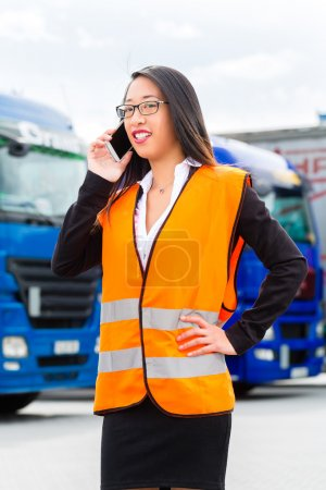 Female forwarder in front of trucks on a depot