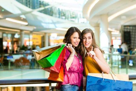 Photo pour Deux amies avec des sacs à provisions s'amusent en faisant du shopping dans un centre commercial - image libre de droit