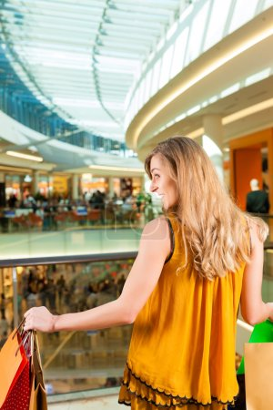 Young woman shopping in mall with bags